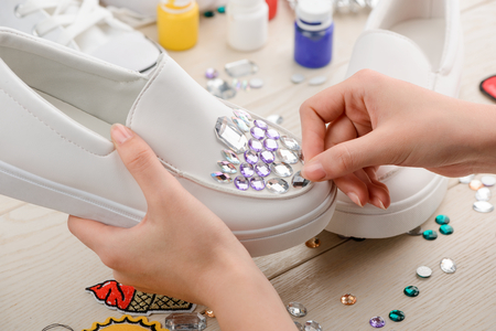 Girl putting rhinestones onto shoes