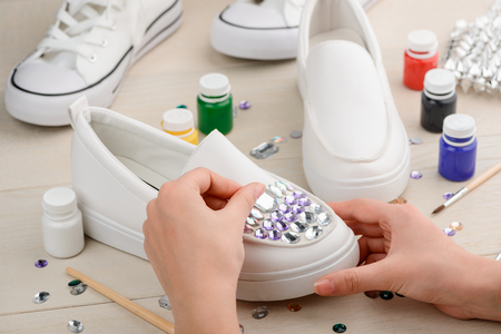 Craftswoman putting rhinestones on shoes Stock Photo