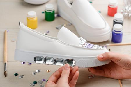 Woman applying rhinestones onto shoes