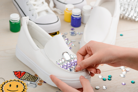 Girl attaching rhinestones to shoes