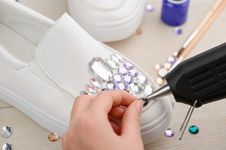 Girl putting rhinestones onto shoe