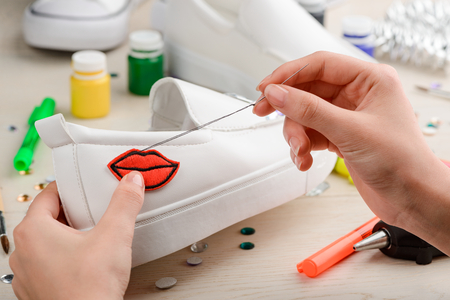 Girl sewing a lips patch