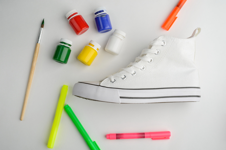 Paint, markers, brush and sneaker