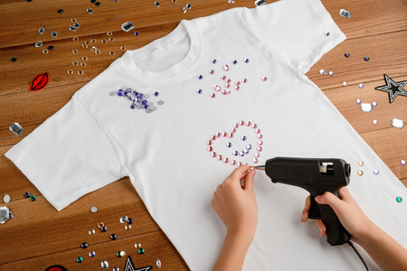 Girl attaching rhinestones to t-shirt
