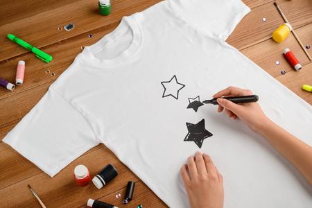 Woman drawing stars on t-shirt