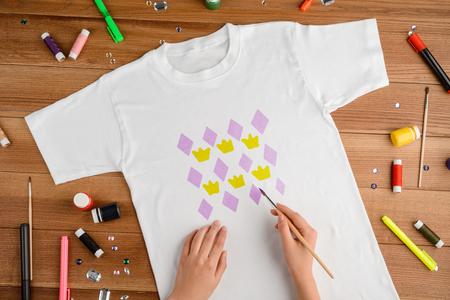 Girl painting pattern on t-shirt Stock fotó