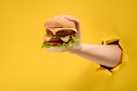 Hand holding a big burger Stock Photo