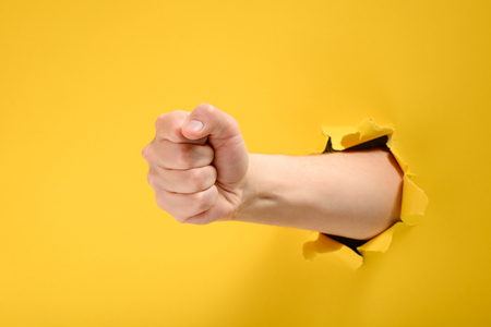 Fist punching through yellow paper 版權商用圖片 - 118736182