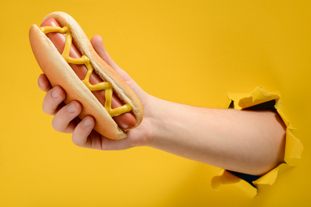 Hand taking a traditional hotdog