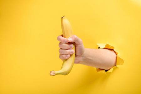 Hand giving a ripe banana