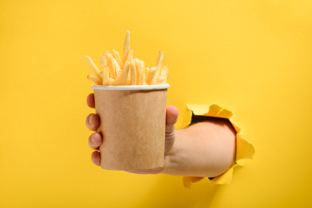 Hand giving French fries Imagens