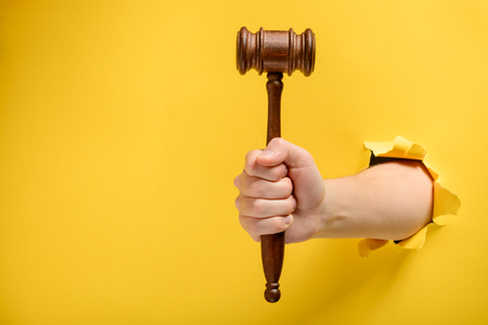 Hand holding a judges gavel