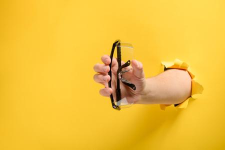 Main donnant des lunettes de sécurité Banque d'images