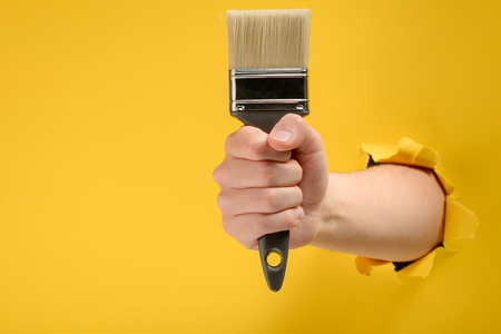 Hand holding a paint brush