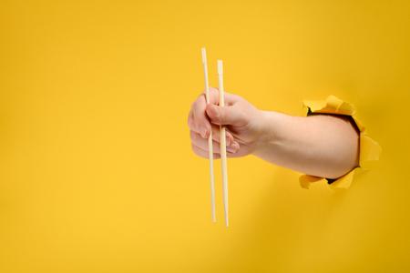 Hand holding wooden chopsticks