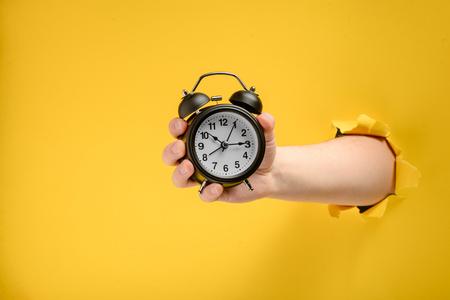Hand hält einen Wecker