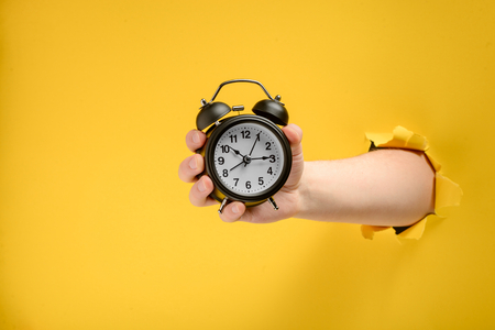 Hand holding an alarm clock Banque d'images