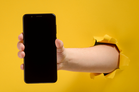 Hand holding a cell phone through torn yellow paper sheet. Blank screen for your design. Gadget mockup.
