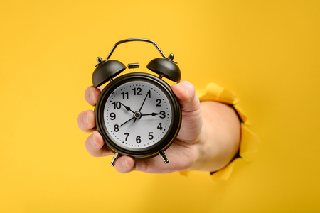 Hand showing an alarm clock out of a hole in torn yellow paper wall. No time to wait. Reklamní fotografie