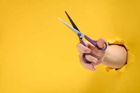 Hand using scissors through torn yellow paper background. Cut off excess. Stationery, office supply.