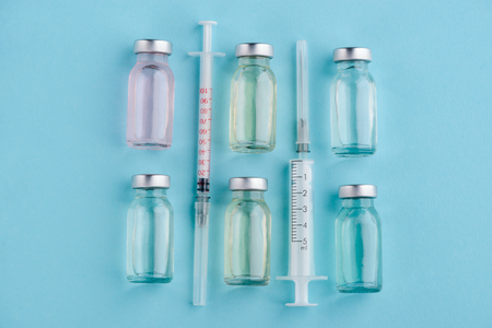 Vaccines and syringes on blue Foto de archivo - 119154348
