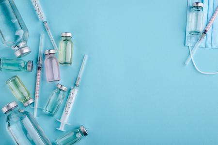 Syringe and vials on blue Foto de archivo - 119155016