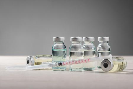 Vials and syringe on gray Reklamní fotografie