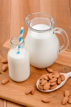 Raw almonds and jug of plant milk on wooden background. Homemade vegan product, good alternative to dairy. 版權商用圖片