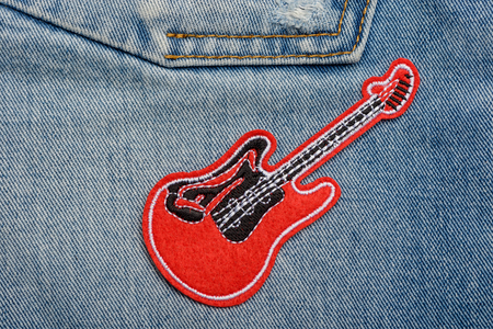 Red guitar patch on jeans