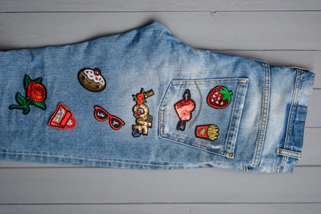Jeans embellished with embroidered patches