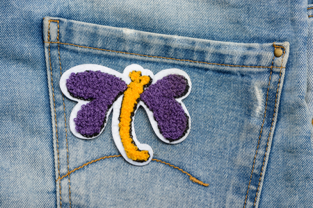 Butterfly fabric patch on jeans