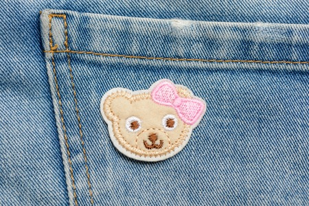 Baby bear patch on jeans Stock Photo