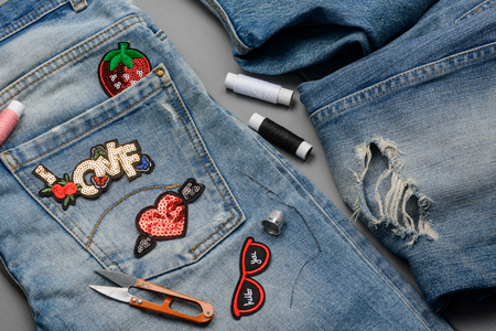 Patches, threads, scissors and jeans Stock Photo