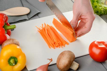 Man cutting a carrot Stock Photo