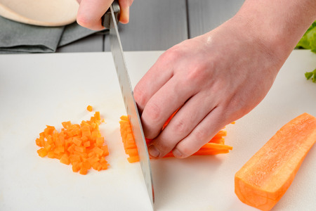 Chef chopping carrot sticks