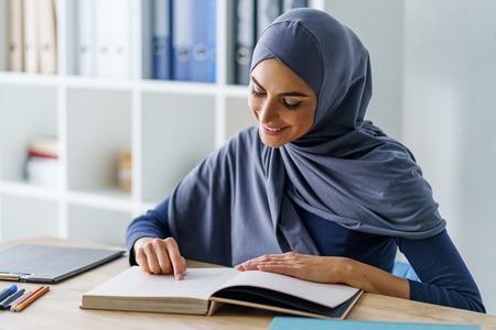 Beautiful Muslim woman reading