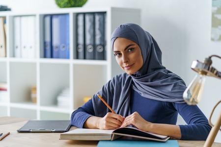 Étudiant musulman assis à table