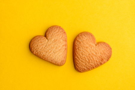 Two heart cookies on yellow
