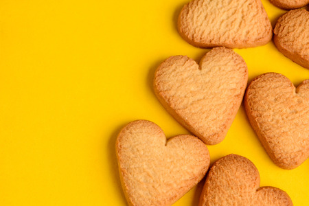 Heart-shaped cookies on yellow background