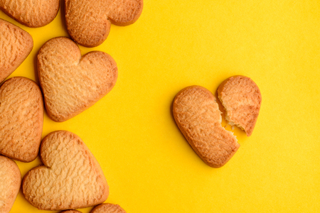 Heart-shaped cookies on yellow background. One biscuit is broken. The end of love, breakup concept.