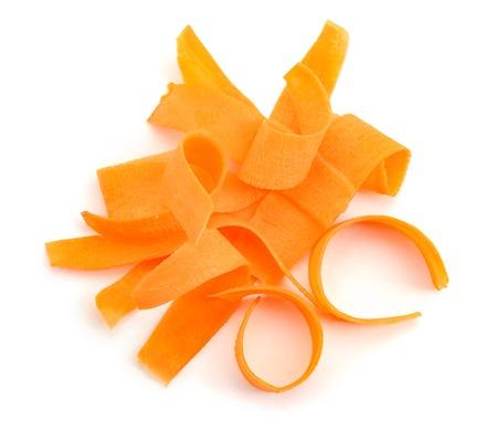Carrot peels on white background. Close up on orange vegetable shavings.