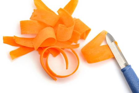 Carrot shavings and peeler knife on white background. Foto de archivo - 120815532