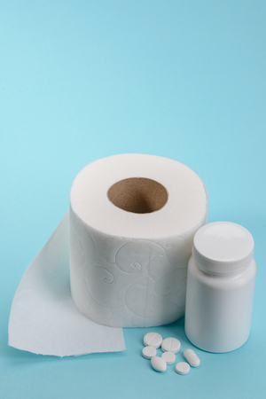 Medical pills and toilet paper on blue background. Normalization of digestion. Constipation or diarrhea treatment.