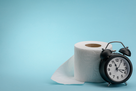 Toilet paper and alarm clock on blue background with copy space. Spending too much time in toilet.