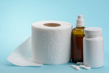 Toilet paper and medicine for constipation on blue background. Treatment to digestive disorder.