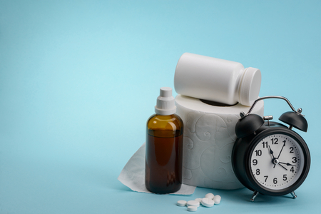 Toilet paper, medicine and alarm clock on blue background with copy space. Laxative drugs to treat constipation immediately.