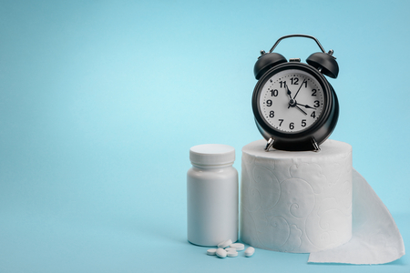 Medical pills, toilet paper and alarm clock on blue background with copy space. Constipation treatment concept.