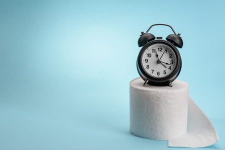 Alarm clock and toilet paper on blue background with copy space. Creative concept of digestion problem. Stock Photo