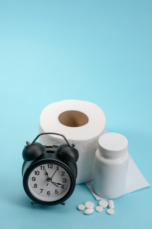 Clock, toilet paper and pills on blue background with copy space. Quick relief from constipation.