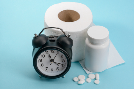 Clock, toilet paper and pills on blue background. Effective treatment from digestive disorders.